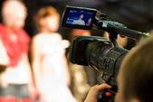Cameraman with digital video camera (shallow DoF) — Stock Photo