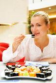 Hermosa chica comiendo sushi en un restaurante — Foto de Stock