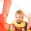 Adorable baby hiding in a kid's tent — Stock Photo