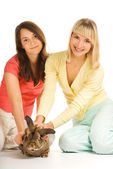 Two girls playing with bunny isolated on white background — Stock Photo