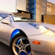 Sport car with office building and clear blue sky behind it — Stock Photo