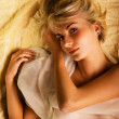 Portrait of a lovely beautiful blond girl lying in a bed — Stock Photo