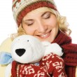 Beautiful girl in winter clothing with a polar bear toy — Stock Photo