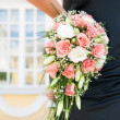Woman's hand holding beautiful bouquet of roses — Stock Photo