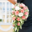 Woman's hand holding beautiful bouquet of roses — Stockfoto