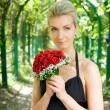 Beautiful blond girl holding bouquet of red roses — Stockfoto