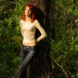 Beautiful redhead girl in the forest — Stock Photo