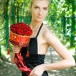 Beautiful blond girl with a bouquet of red roses — Stock Photo #4903506
