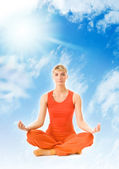 Beautiful young woman meditating in the sky — Stock Photo