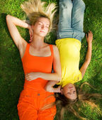Two girls lying on a meadow — Stock Photo