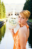 Beautiful redhead woman with bouquet of flowers — Stock Photo