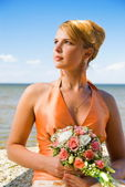 Lovely redhead lady with a bouquet of flowers near the sea — Stock Photo