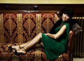 Beautiful brunette sitting on a luxury sofa — Stock Photo