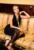 Sexy ragazza bionda seduta su un divano di lusso — Foto Stock