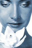 Close-up portrait of a beutiful girl with white orchid (toned in — Stock Photo