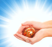 Hands holding easter egg on abstract blue background — Stock Photo
