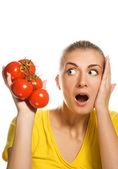 Shocked girl with fresh tomatoes — Stock Photo
