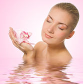 Blond girl with pink orchid reflected in rendered water — Stock Photo