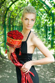 Beautiful blond girl with a bouquet of red roses — Stock Photo
