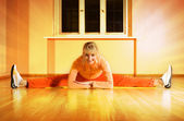 Beautiful fitness trainer does splits on a floor surrounded by t — Stock Photo