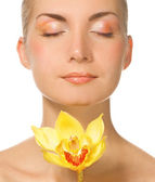 Portait of a lovely lady with yellow orchid — Stock Photo
