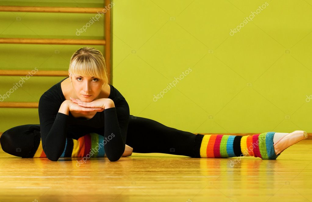 Ballet dancer doing stretching exercise on a floor — Stockfoto #4903105