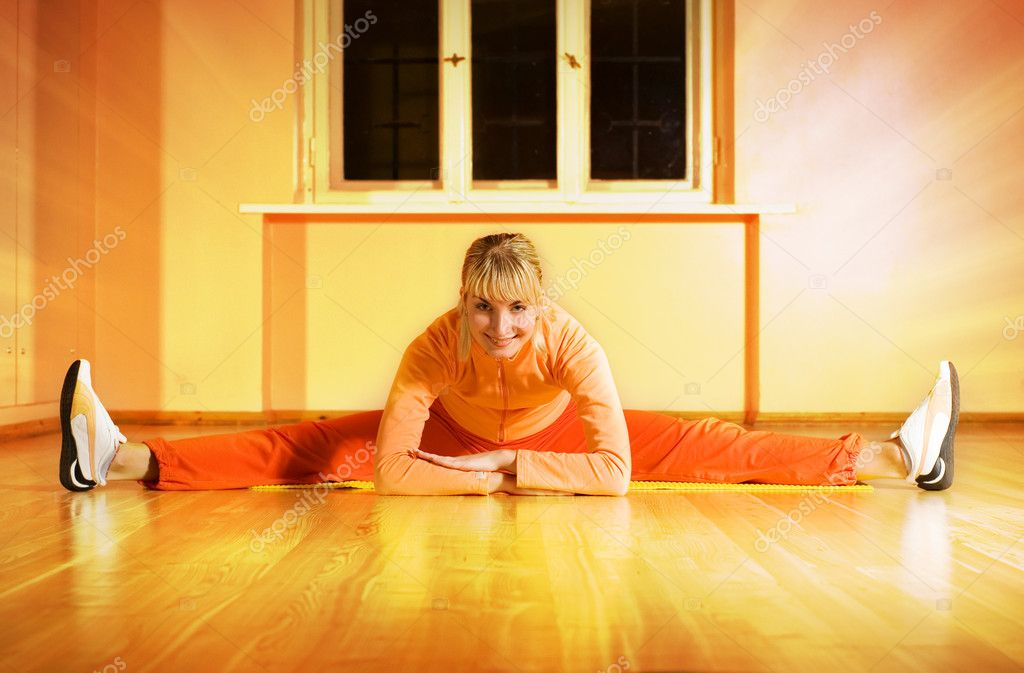 Beautiful fitness trainer does splits on a floor surrounded by the magic light — Stock Photo #4903566