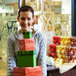 Teenager girl with gift boxes in a shop — Stock Photo