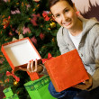 Teenager girl with gift boxes, Christmas three behind her — Stock Photo #4959156