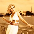 Beautiful blond girl drinks champagne near the river at sunset t — Foto de Stock
