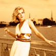 Beautiful blond girl drinks champagne near the river at sunset t — Stok fotoğraf