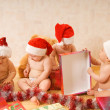 Royalty-Free Stock Photo: Group of adorable toddlers in Christmas hats packing presents