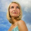 Beautiful blond girl and blue cloudy sky behind her — Stock Photo
