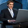 Handsome confident businessman working on his laptop in front of — Stock Photo