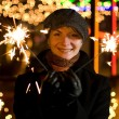 Beautiful happy girl with Christmas fireworks on abstract blurre — Stock Photo #4959404