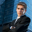Stock Photo: Young confident business man posing in front of office building