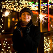Beautiful happy girl with Christmas fireworks on abstract blurre — Stock Photo