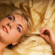 Portrait of a lovely beautiful blond girl lying in a bed - Stock Photo