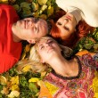 Three friends lying on autumn leaves — Stock Photo