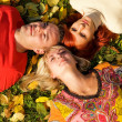 Stock Photo: Three friends lying on autumn leaves