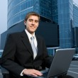Business man sitting in front of the office building and working — Stock Photo