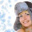 Lovely blond girl in winter fur-cap and abstract snowflakes arou — Stock Photo