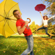 Funny couple with umbrellas on autumn background (focus on a guy — Stock Photo