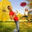 Funny couple with umbrellas on autumn background (focus on a guy — Stock Photo #4959809