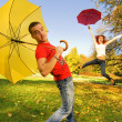 Funny couple with umbrellas on autumn background (focus on a guy — Stock Photo #4959829