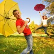 Royalty-Free Stock Photo: Funny couple with umbrellas on autumn background (focus on a guy