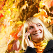Happy girl talks to on the phone, autumn background behind her - Stock Photo