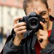 Handsome guy with a digital camera - Stok fotoğraf