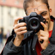 Handsome guy with a digital camera - Stock Photo