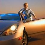 chico guapo cerca del coche del deporte moderno al atardecer — Foto de Stock   #4959912